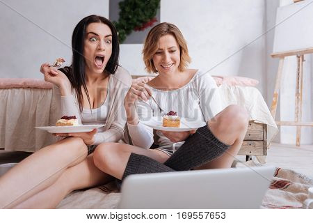 What a plot twist. Emotional brunette goofy woman seeming excited while she and her friend watching a movie and eating their morning meal