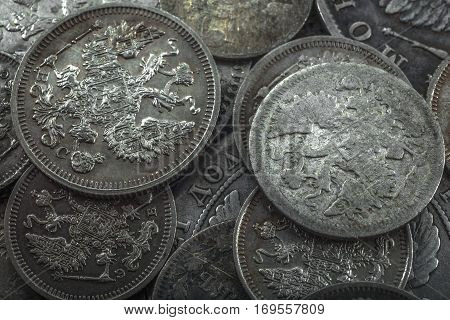 old silver coins of the Russian Empire lie in bulk in dim lighting