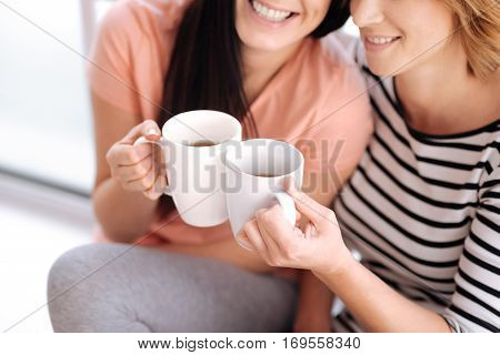 Delightful taste. Positive graceful smiling women sitting by the window on a sill and holding up cups with morning drinks and enjoying the warm sunlight