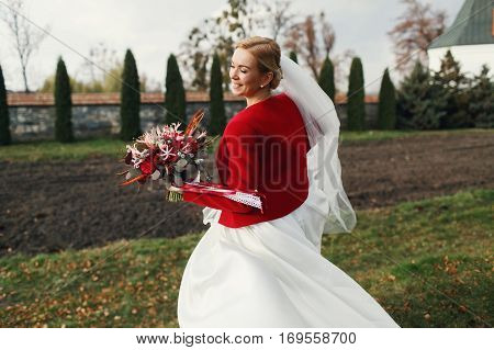 Smiling Bide In Red Jacket Turns Around Holding An Autumn Bouquet