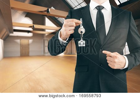 Businessman holding key with house keychain in modern loft interior with wooden floor. Real estate concept. 3D Rendering