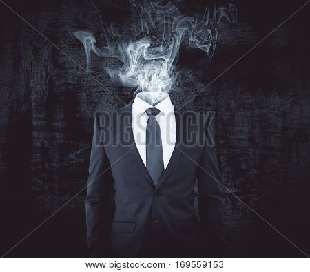 Businessman with smoke intead of head on dark background. Confusion concept