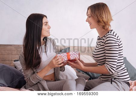 You remembered. Tender joyful young woman giving her excited girlfriend a gift while staying at home all weekend and celebrating their first anniversary