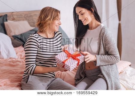 Is this for me. Interested pleased pretty woman trying opening a cute gift her girlfriend presenting her while sitting on a bed and enjoying the moment