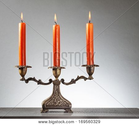 Antique bronze candlestick with three burning orange candles on gray background