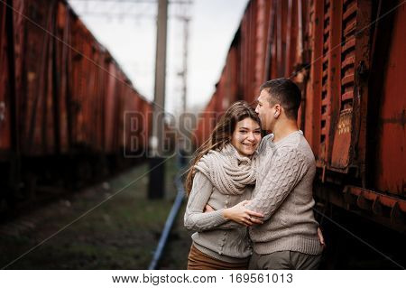 Smiling Girl With Braces. Yong Couple Wearing On Tied Warm Sweaters Hugging In Love At Railway Stati