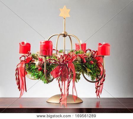 Vintage advent wreath with four burning red candles and gold star on gray background lights and decoration for christmas time