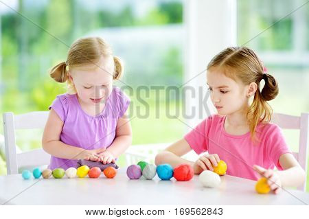 Two Cute Little Sisters Having Fun Together With Modeling Clay At A Daycare. Creative Kids Molding A