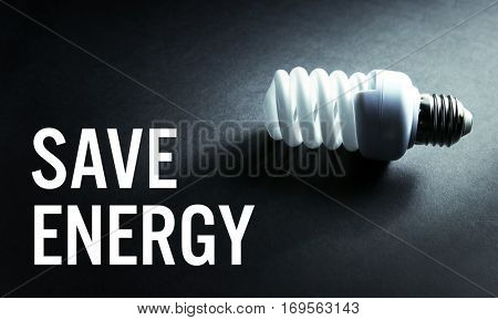 Light bulb and text SAVE ENERGY on dark background