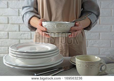 Female hands holding porcelain dishware, closeup