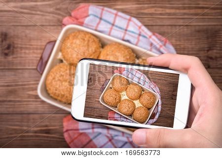 Hands taking photo chicken cheese sliders with smartphone.