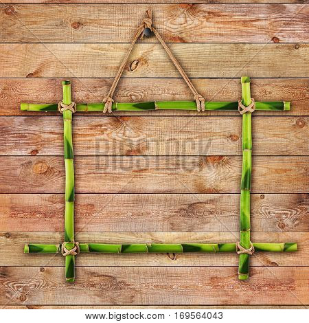 Green bamboo frame on natural wooden surface. Closeup.