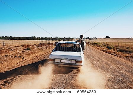 3 guys on a road trip along a Rural dirt road in the desert