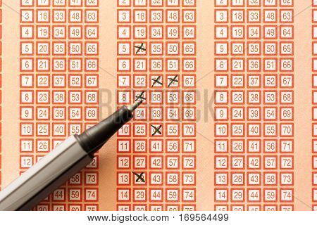 pen and bingo lotto lottery ticket with crossed numbers
