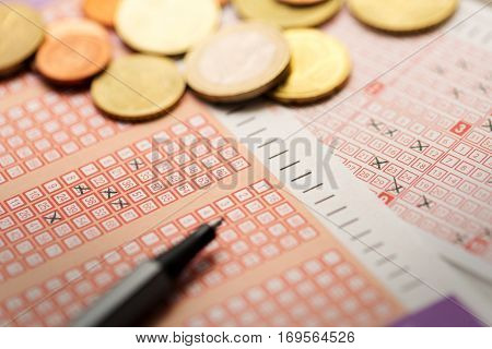 bingo lotto lottery tickets with coins and pen