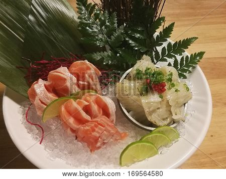 Special Deluxe Combination sashimi set Salmon Engawa and seaweed on ice sever with wasabi and lime traditional Japanese food