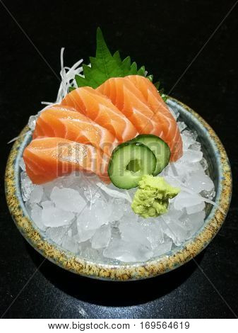 Special Deluxe salmon sashimi set on ice sever with wasabi and cucumber traditional Japanese food top view