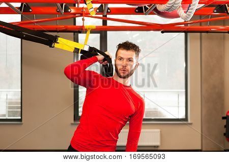 TRX concept. Handsam man exercising her muscles with help of suspension trainer sling or suspension straps isolated on white background.