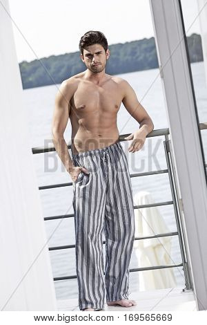 Full length portrait of muscular young man in pajama leaning on railing of hotel balcony