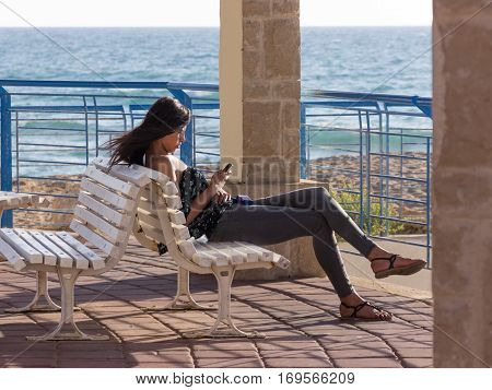 Nahariya Israel - May 30 2016: Young girl sits on a sunset on the beach and wrote a message on a mobile phone in Nahariya Israel