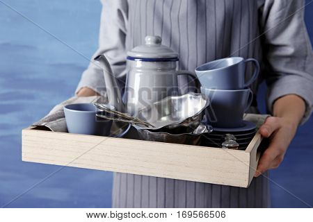 Closeup of female hands holding wooden tray with dishware