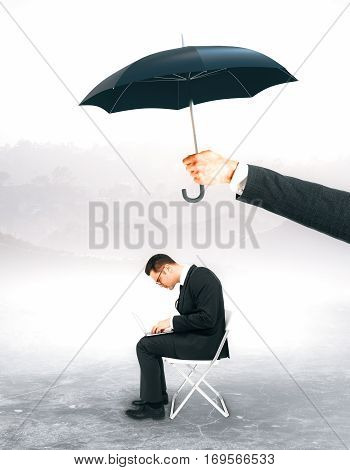 Hand holding umbrella over working businessman. Protection concept. Landscape background