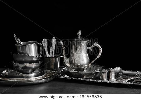 Silver dishware on table and black background