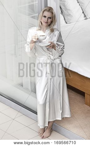 Full length of beautiful young woman in robe drinking coffee at balcony doorway