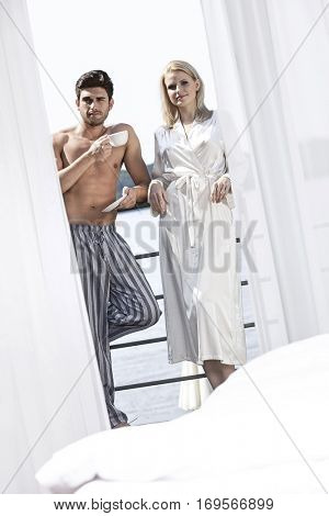 Portrait of young couple in sleepwear relaxing at hotel balcony