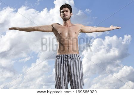 Young muscular man standing arms outstretched against cloudy sky