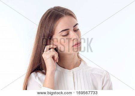 young girl who closed her eyes and kept the ball for the ear is isolated on a white background