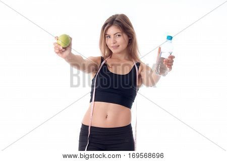 Beautiful slim girl in a black top and tights standing straight and holding out both hands forward shows a fruit and a bottle of water