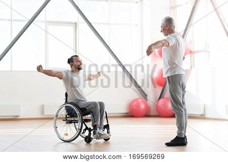 Working out together. Involved smiling young disabled man listening to his physical therapist and having a training session while expressing positivity and sitting in the wheelchair