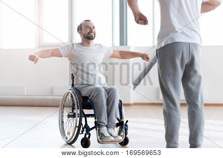 My everyday physical therapy. Hardworking delighted positive disabled man repeating exercises after the orthopedist and having a training session while smiling and sitting in the wheelchair