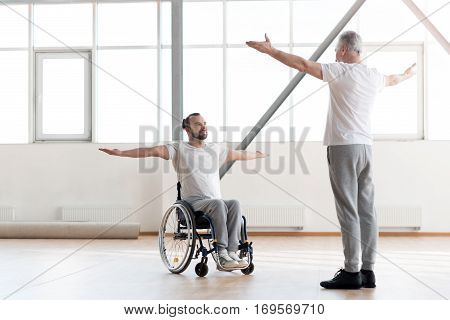 My everyday alternative therapy. Hardworking charming positive disabled man repeating exercises after the coach and exercising while sitting in the wheelchair