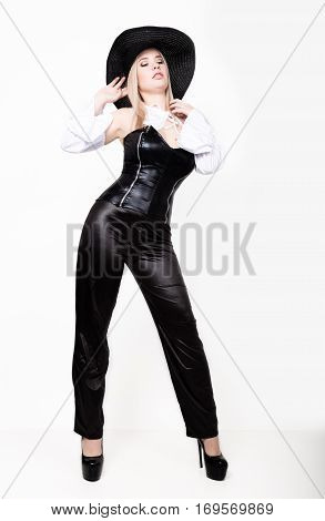 sexy woman with hourglass figure dressed in black leather corset and pants with wide-brimmed hat.