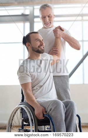 Enjoying helping people. Masterful positive aged physical therapist helping the disabled man doing exercises and providing a rehabilitation while expressing interaction and expressing positivity