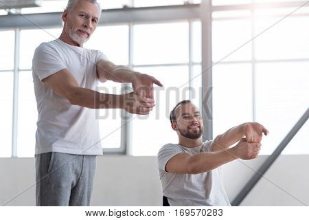 Caring about our health together. Athletic positive aged physical therapist teaching the disabled man doing physical exercises and providing a rehabilitation session while expressing positivity