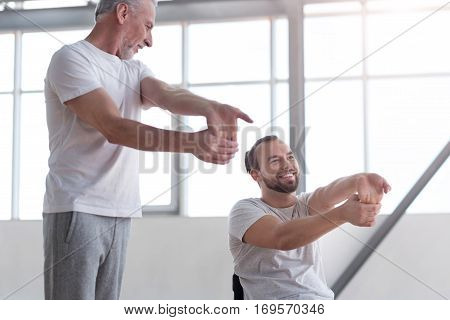 Supporting my disabled friend. Athletic smiling aged physical therapist teaching the disabled man doing physical exercises and providing a rehabilitation session while expressing positivity