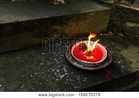 Beautiful red candle burning on the stone steps
