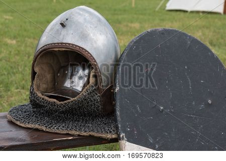 Silver and Metallic Knight Helmet on Wooden Table near Black Shield Medieval Theme