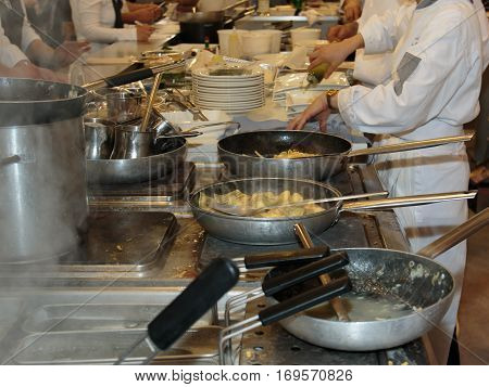 Cooking Inside Restaurant's Kitchen, Pans And Chef With Uniform