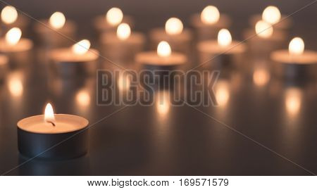 Flame of many candles burning on the background in light brown and yellow color - sadness