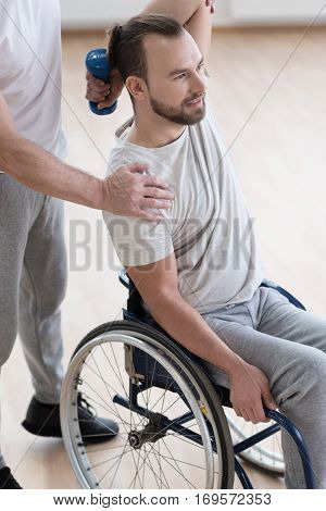 Full of concentration. Flexible involved young disabled man holding the dumbbell and having the lesson with the orthopedist while having the physical therapy session and expressing concentration