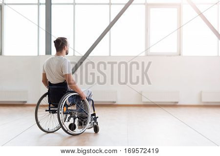 Thinking about my future. Thoughtful involved young disabled man sitting in the wheelchair in the gym and looking at the window while expressing concentration