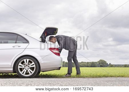 Full length side view of young businessman looking in car trunk at countryside