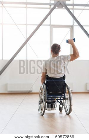 Working out hours. Athletic powerful young invalid sitting in the wheelchair in the gym and looking at the window while exercising and holding the dumbbell