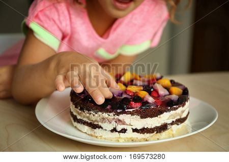 Little girl tasting cream of sweet cake left on kitchen table, close up view