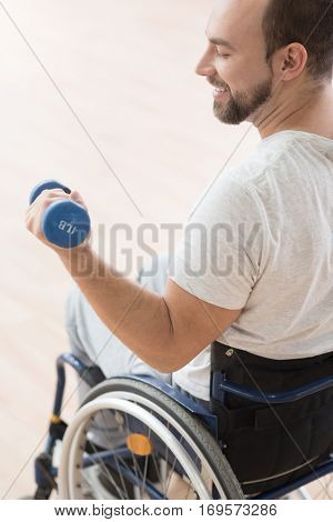 Full of happiness. Muscular smiling athletic invalid sitting in the wheelchair in the gym and looking at his arm while exercising and holding the dumbbell