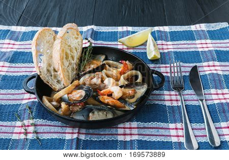 Seafood Stew in Saucepan. Authentic italian restaurant cuisine, healthy delicatessen food. Oysters, shrimps, calamari in white cream sauce with bruschetta. Bowl closeup on served table